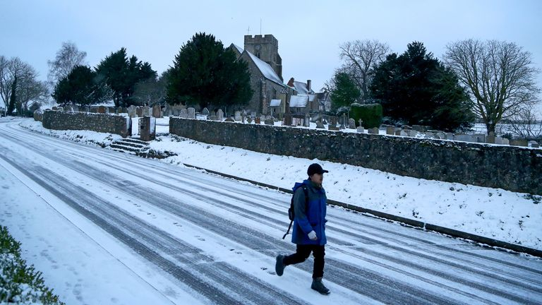 A man walks to work along a road covered in snow in Great Chart, near Ashford in Kent