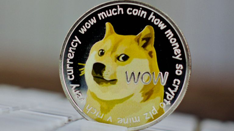 Digital currency physical metal dogecoin coin on white computer keyboaed.