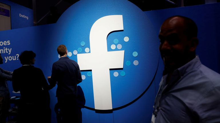 Attendees walk past a Facebook logo during Facebook Inc's F8 developers conference in San Jose, California