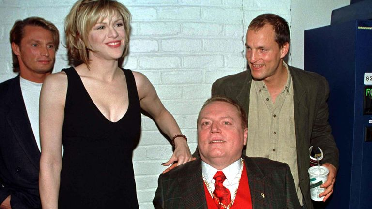 """Magazine publisher Larry Flynt (in wheelchair) poses with the cast of the new film based on his life """"The People vs. Larry Flynt"""" during a special screening of the film December 2 in Los Angeles. Shown (L-R) are Brett Harrelson, who portrays Jimmy Flynt, actress Courtney Love who portrays Larry Flynt's wife Althea and Woody Harrelson who plays Larry Flynt in the film."""