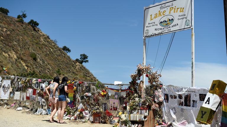 """""""Glee"""" fans Haley Deeds, left, and her sister Kaela, of Ventura, Calif., visit a makeshift memorial for the late """"Glee"""" cast member Naya Rivera at Lake Piru, Monday, Aug. 3, 2020, in Los Padres National Forest, Calif., about 55 miles (90 kilometers) northwest of Los Angeles. The 33-year-old actress was found dead in Lake Piru on July 13, five days after her son, Josey, was found alone on a boat the two had rented there. (AP Photo/Chris Pizzello)"""
