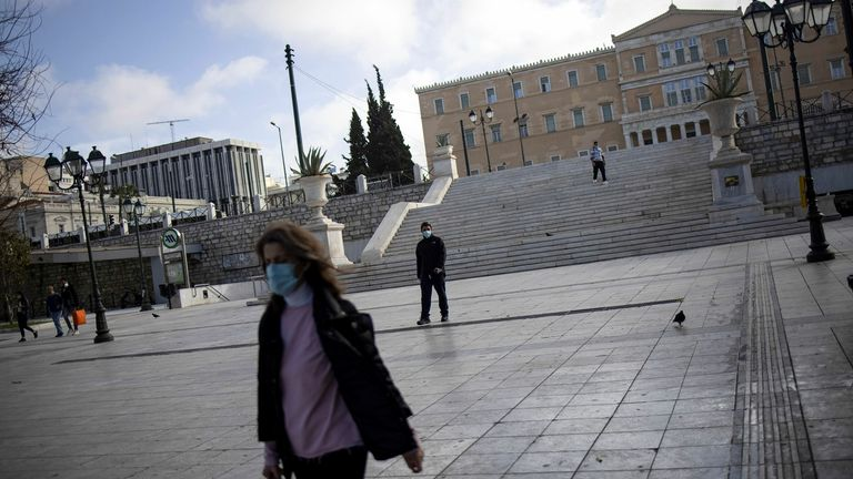 People wearing protective masks walk on Syntagma square, after the Greek government imposed stricter lockdown measures to curb the spread of the coronavirus disease (COVID-19) pandemic, in Athens, Greece, February 11, 2021. REUTERS/Alkis Konstantinidis