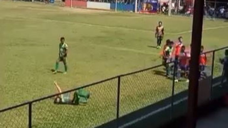 Football player fakes being hit by object thrown on to pitch during match in Guatemala