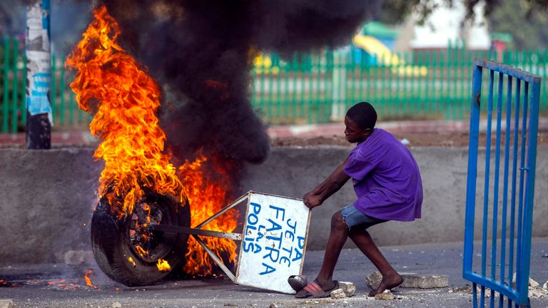 """A boy drags a sign reading in Creole """"Do not throw trash here. The Police,"""" in Port-au-Prince, Haiti. Pic: AP"""