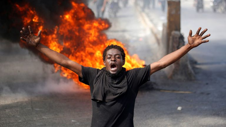 A demonstrator shouts past a barricade during a march protest against Haiti's President Jovenel Moise, in Port-au-Prince, Haiti February 14, 2021. REUTERS/Jeanty Junior Augustin