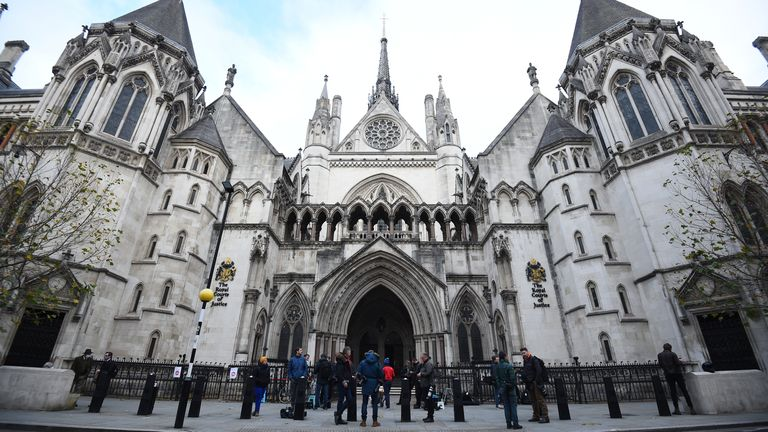 Members of the press wait outside the Royal Courts of Justice, in central London