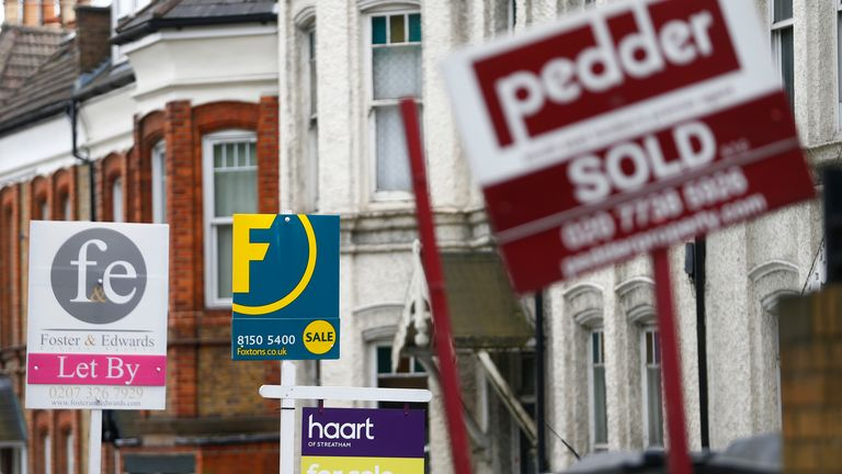 Estate agents boards are lined up outside houses in south London June 3, 2014