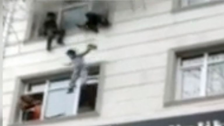 One of four children is dropped from an apartment window to bystanders below after a fire broke out, Thursday, Feb. 25, 2021, in Istanbul, Turkey. (IHA via AP)