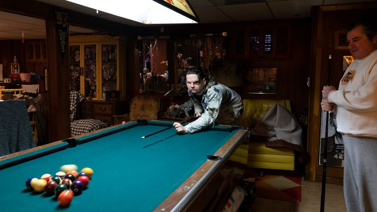 Joe DiMeo plays pool with his father John at their home, Thursday, Jan. 28, 2021, in Clark, N.J., six months after an extremely rare double hand and face transplant. Back in 2018, DiMeo fell asleep at the wheel, he said, losing control of his car, which hit a curb and utility pole, flipped over, and burst into flames. (AP Photo/Mark Lennihan)