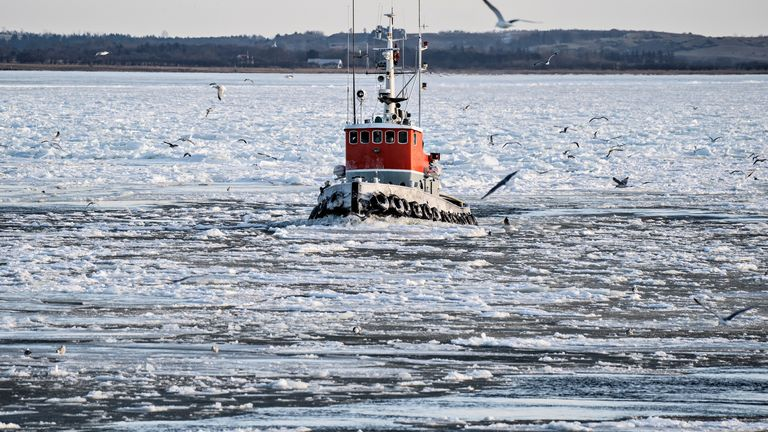 A tugboat breaks the ice formations in the water of the fjord, Limfjorden, near Aggersund, in North Jutland, Denmark February 10, 2021