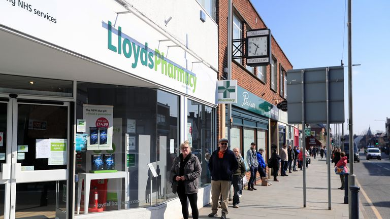 Members of the public queue to enter a Lloyds Pharmacy in Melton Mowbray, allowing a two metre gap between individuals as the UK continues in lockdown to help curb the spread of the coronavirus.