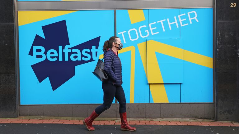 A woman wearing a face mask walks past a public information sign in Belfast as Northern Ireland remains in an extended lockdown to curb the spread of coronavirus and lower infection rates.