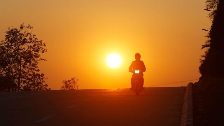 A man rides his motorbike during sunset in Naypyitaw, Myanmar. Pic: AP