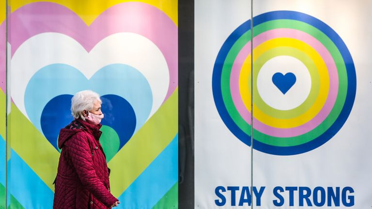 A woman wearing a protective face mask walks past a sign in a Primark shop window in Brighton that says 'Stay Strong', as the UK continues in lockdown due to the coronavirus pandemic. Picture date: Friday February 5, 2021.