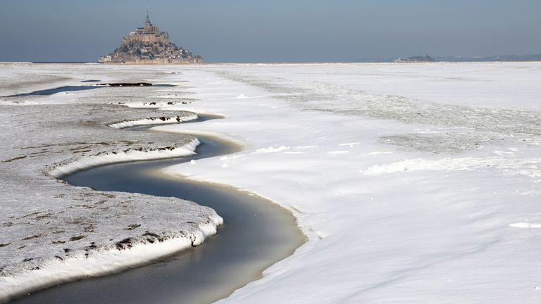 A view shows the snow-covered Bay of Mont Saint-Michel in the French western region of Normandy, as winter weather with snow and cold temperatures hits a large northern part of the country, France, February 10, 2021