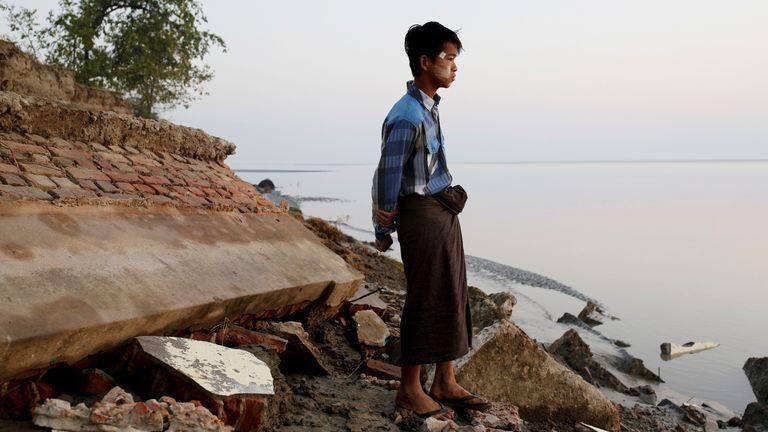 Seorang siswa berdiri di dekat reruntuhan sekolah setelah sekolah itu jatuh ke air di Myanmar