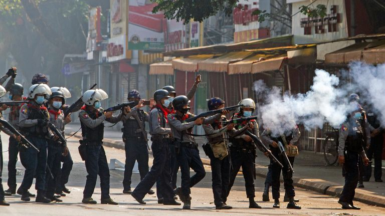 Riot police officers fire teargas canisters during a protest in Yangon
