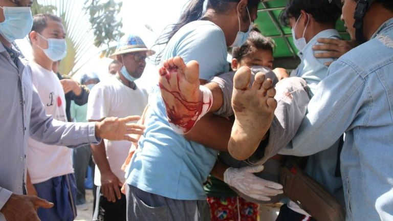 A wounded protester is carried amid protests in Dawei