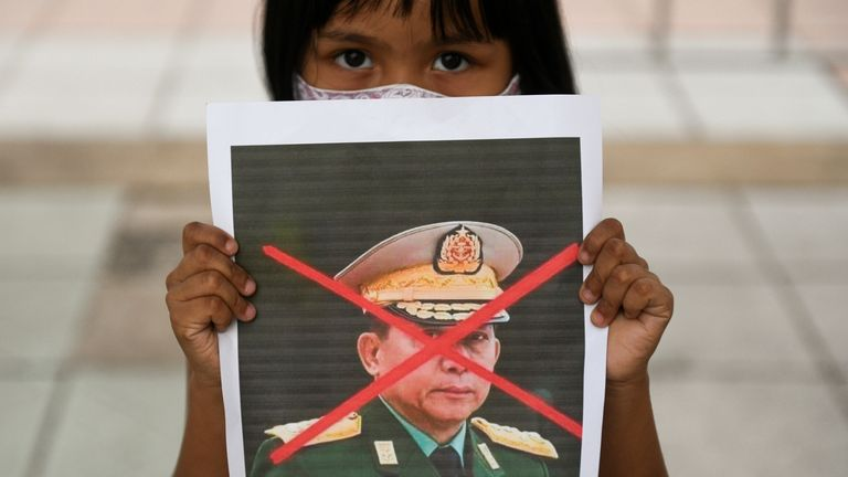 A girl holds a picture of Myanmar's army chief Min Aung Hlaing with his face crossed out as Myanmar citizens protest against the military coup in Myanmar outside United Nations venue in Bangkok, Thailand February 6, 2021. REUTERS/Chalinee Thirasupa