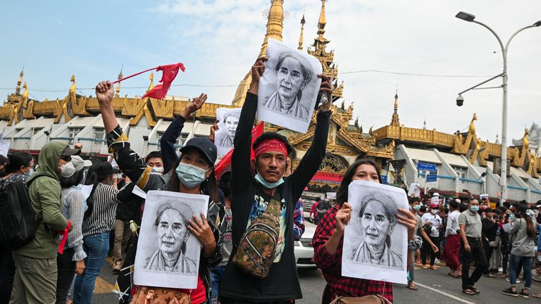 People in Yangon hold pictures of jailed leader Aung San Suu Kyi