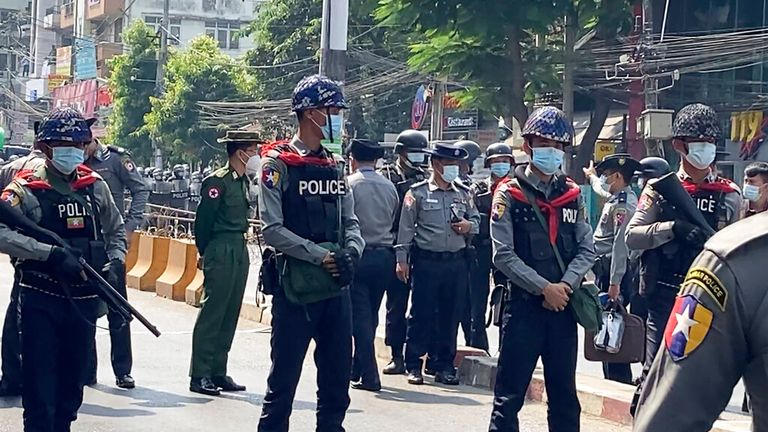Officers block the road to stop protesters marching forward in Yangon, Myanmar