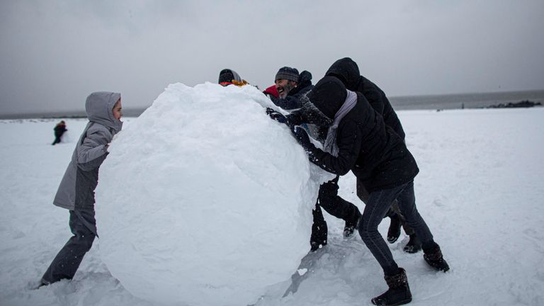 People make a giant snow ball during a winter storm at Brighton Beach, New York