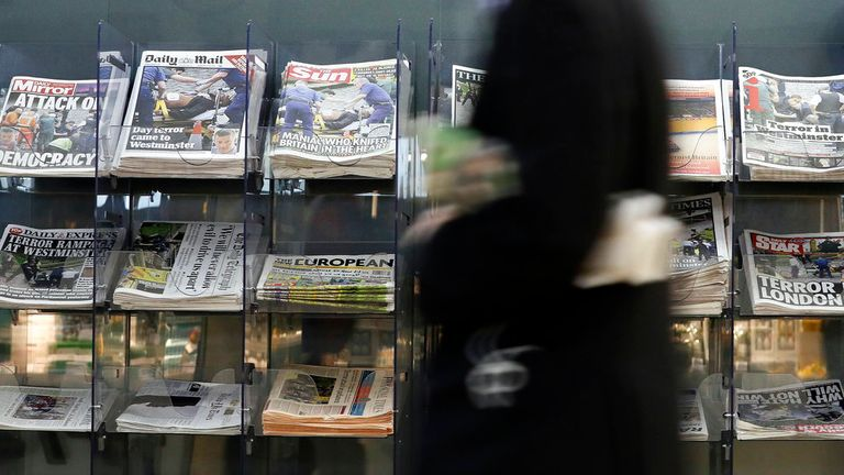 A man passes a newspaper stand showing coverage of Wednesday's attack in London, Thursday March 23, 2017. On Wednesday a knife-wielding man went on a deadly rampage, first driving a car into pedestrians before stabbing a police officer to death and then was fatally shot by police within Parliament's grounds in London. Five people were killed, including the assailant.(AP Photo/Kirsty Wigglesworth)