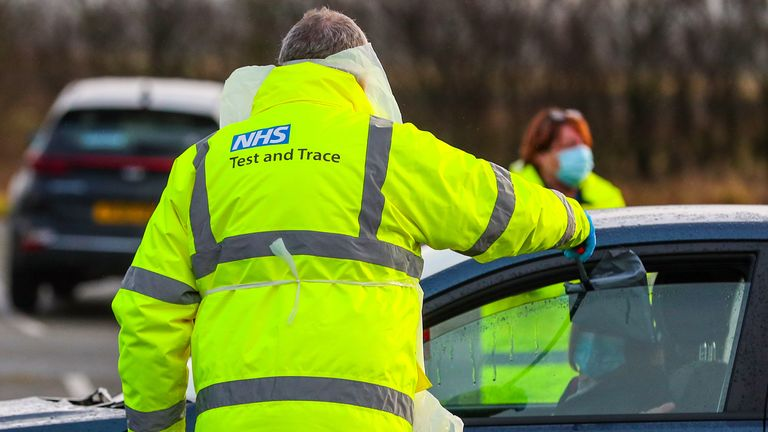 An NHS Test and Trace worker hands a person a test kit in a drive-through testing centre in Southport