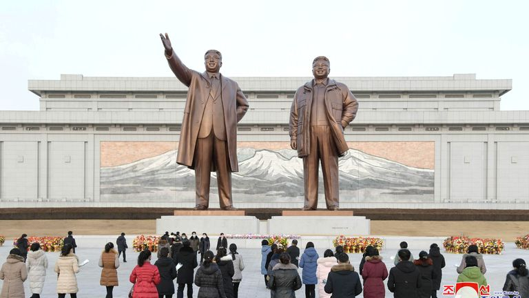 Flowers are laid in front of the bronze statues of Kim Il Sung and his son Kim Jong Il on the Day of the Shining Star, the birth anniversary of Kim Jong Il