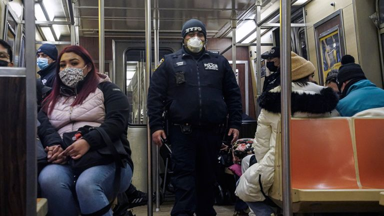 Police patrol the A line subway train bound to Innwood, after NYPD deployed an additional 500 officers into the subway system following deadly attacks, Saturday Feb. 13, 2021, in New York.  Authorities say an unidentified man could be responsible for four separate stabbing attacks in the New York City subways that have left two people dead. New York police say the assaults happened between Friday morning and early Saturday. (AP Photo/Bebeto Matthews)