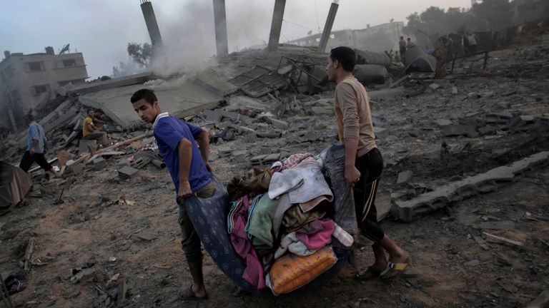 Palestinians near their ruined house destroyed by an overnight Israeli airstrike in Gaza City in July 2014