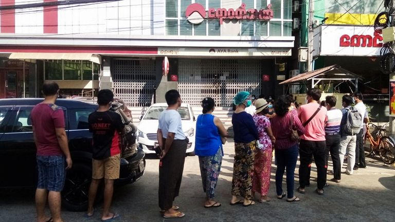 People line up outside a bank branch in Yangon, Myanmar