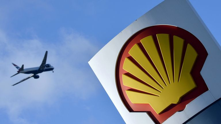 A passenger plane flies over a Shell logo at a petrol station in west London, January 29, 2015. REUTERS/