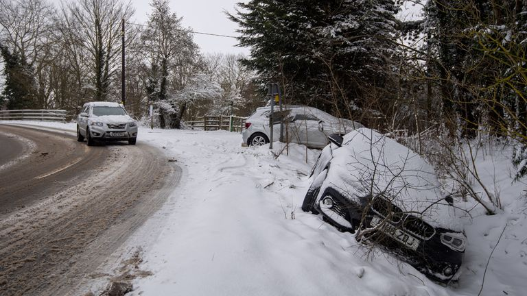 Abandoned cars in a snow filled ditch in Needham Market in Suffolk