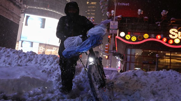 A delivery biker navigates a snow drift during a snow storm in New York