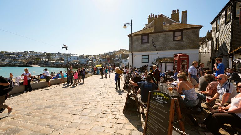 """istock - """"St Ives, United Kingdom - April 28, 2011: Tourists enjoying the sun at the waterfront in St Ives, Cornwall.St. Ives is a small picturesque town popular with tourists in the southwest of England."""""""