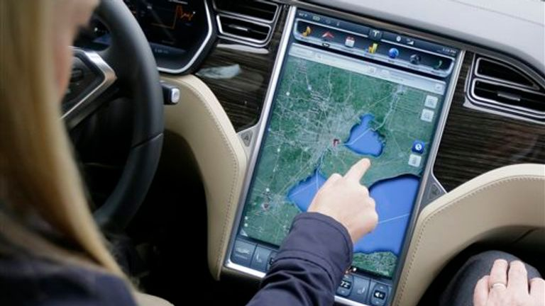 In this Tuesday, April 7, 2015 photo, Alexis Georgeson of Tesla Motors shows off the navigation screen during test drive of the new Tesla Model S 70-D electric car in Detroit. Tesla is going after mainstream luxury car buyers by boosting the range, power and price of its low-end Model S. The $75,000 all-wheel-drive 70-D can go a government-certified 240 miles per charge, has 514 horsepower and can go from zero to 60 in 5.2 seconds. (AP Photo/Carlos Osorio)