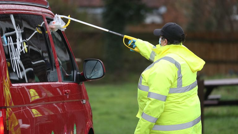 A test and trace worker in the Bramley Inn car park in Bramley, near Basingstoke, Hampshire takes a coronavirus test from a driver at a surge testing programme with local residents, after a case of the South African variant of Covid-19 was identified in the village. Picture date: Wednesday February 17, 2021.