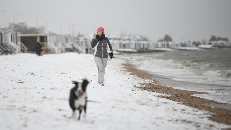 A woman walks a dog along a snow covered beach at Thorpe Bay, Essex, as bitterly cold winds continue to grip much of the nation. Picture date: Tuesday February 9, 2021.