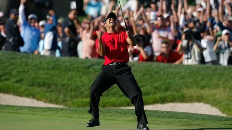 Tiger Woods celebrates after making a birdie on the 18th hole