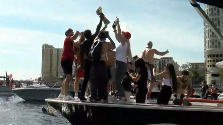 Tom Brady's teammates gather round the Vince Lombardi trophy after he threw it to them from another boat. Pic: WFTS-TV