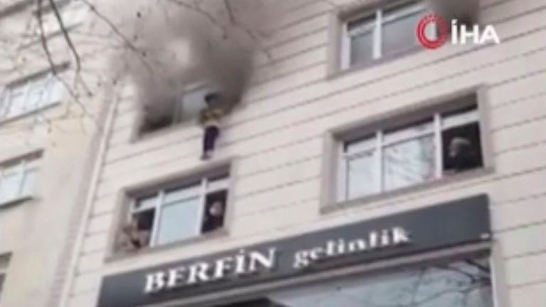 In this image taken from video provided by IHA, one of four children is dropped from an apartment window to bystanders below after a fire broke out, Thursday, Feb. 25, 2021, in Istanbul, Turkey. Pic: AP