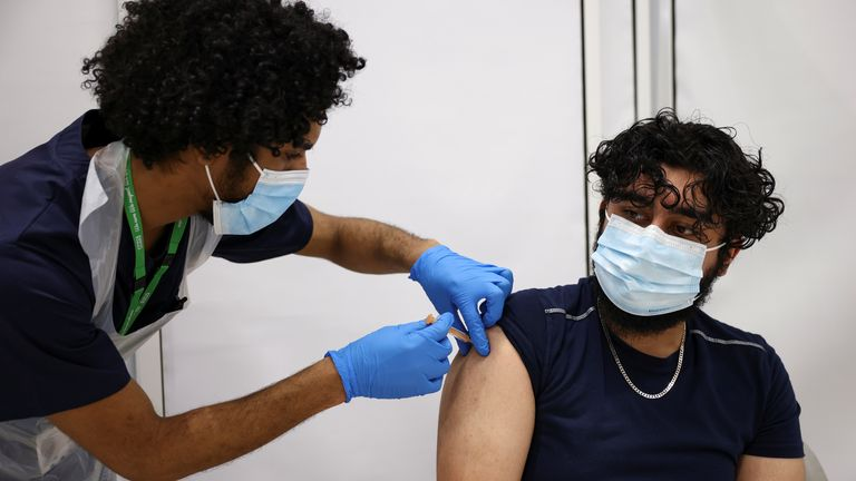 A person gets the coronavirus vaccine, at a vaccination centre in Westfield Stratford City shopping centre, amid the outbreak of coronavirus disease (COVID-19), in London, Britain, February 18, 2021. REUTERS/Henry Nicholls