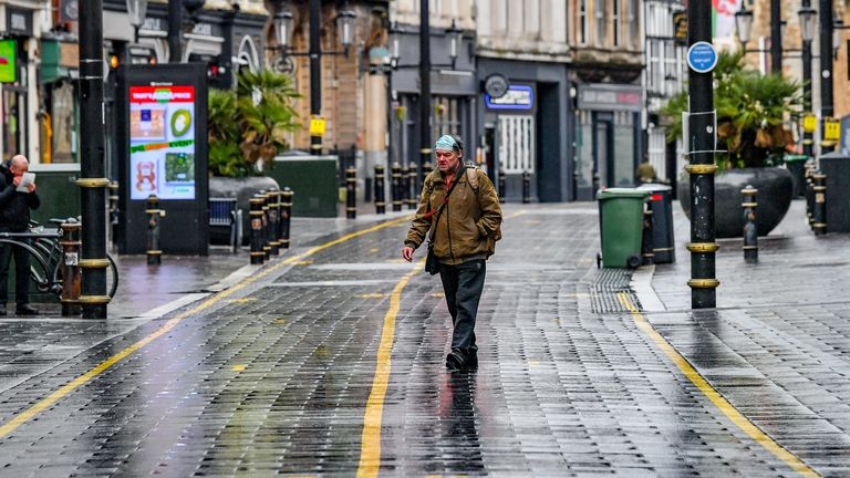 A man wears a facemask on his head in an almost empty central shopping area of Cardiff, Wales, where they are in alert level 4 lockdown on the first weekend of January sales, with many shops not open to browse.