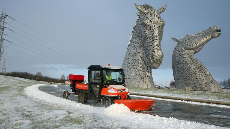 A staff member uses a vehicle to clear snow on a pathway at the Kelpies near Falkirk in Scotland