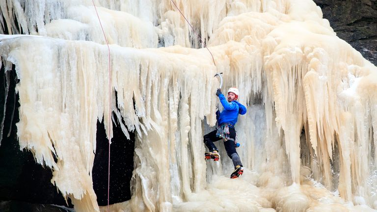 A man ice climbing on the frozen Kinder Downfall, High Peak in Derbyshire