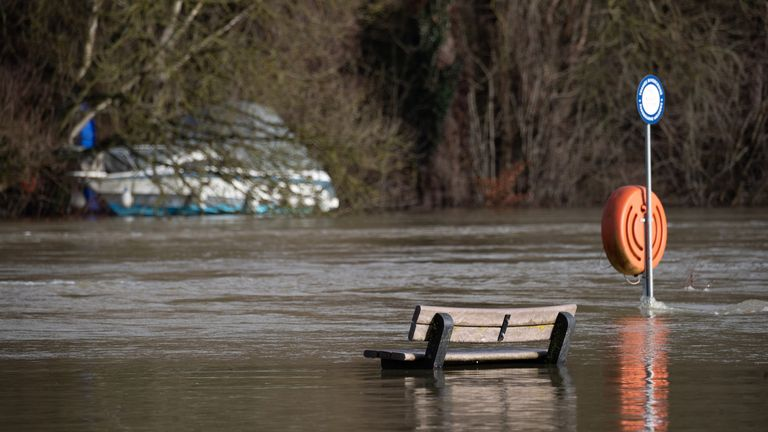 Flooding submerges a park bench along the River Thames in Berkshire
