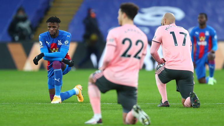 Crystal Palace's Wilfried Zaha kneels