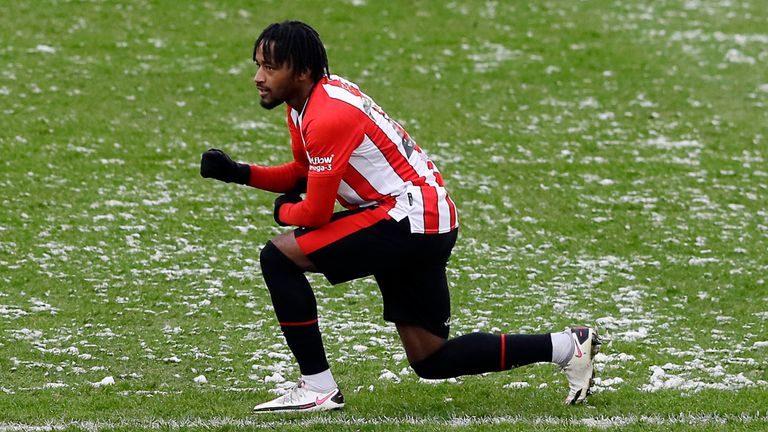 Leicester's Cengiz Under, left, and Brentford's Tariqe Fosu take a knee before the start of the English FA Cup fourth round soccer match between Brentford FC and Leicester City at Brentford Community stadium in London, Sunday, Jan. 24, 2021. (AP Photo/Kirsty Wigglesworth)