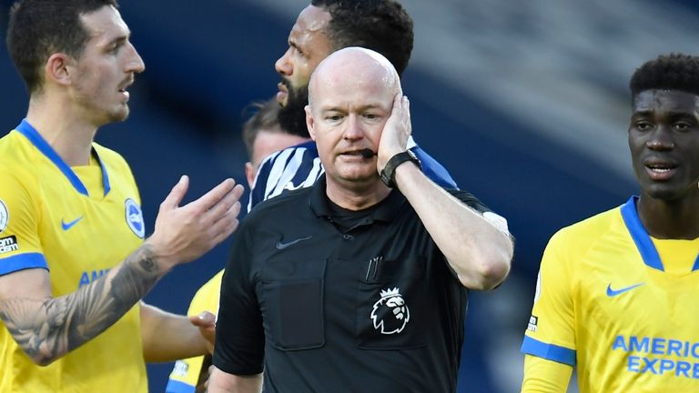 Referee Lee Mason confers with VAR over Lewis Dunk's disallowed free kick (AP)
